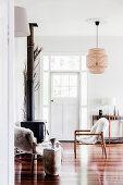 Zwei Stühle mit Tierfell vor Kaminofen in weißem Wohnzimmer
