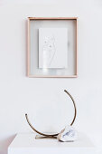 Framed drawing on white wall, including designer brass vase and natural stone