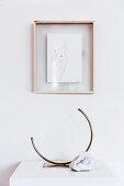 Gerahmte Zeichnung an weißer Wand, darunter Designer-Messingvase und Naturstein