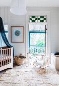 Mobile und Babywiege vor Balkontür und Gitterbett mit Baldachin im Babyzimmer
