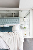 Double bed with high headboard in front of mirrored wall