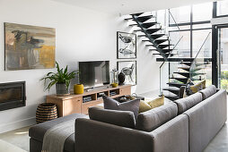 Grey sofa with scatter cushions on TV cabinet in open-plan interior with glass wall and staircase
