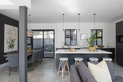 Kitchen island with barstools, dining table with grey upholstered chairs in open-plan interior