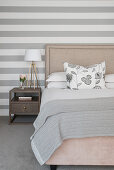 Doppelbett und Nachttisch vor grau-weiß gestreifter Tapete im Schlafzimmer