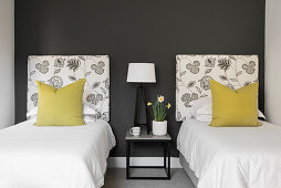 Twin beds and bedside table in guest room with dark wall