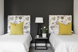 Zwei Einzelbetten und ein Nachttisch im Gästezimmer mit dunkler Wand
