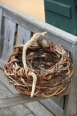 Roughly woven basket made from wicker and gnarled branch