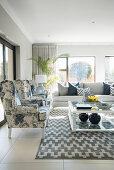Restaurierte Ohrensessel, Glas-Couchtisch und Sofa in hellem Wohnzimmer mit grau-weißem Teppich