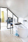 Free-standing bathtub in ensuite attic bathroom with glass wall