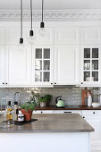 Pendant lamps above island counter in white country-house kitchen