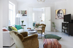 Old armchair in living room with white floor, fresh accents of colour and open double doors
