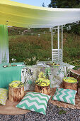 Set table, tree-stump stools and cushions under awning