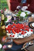 Torte mit Himbeeren auf gedecktem Tisch zum Sommerfest