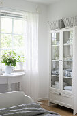 Linen in glass-fronted cabinet in bedroom decorated entirely in white