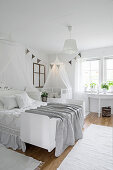 Cot and child's bed in parent's bedroom decorated entirely in white