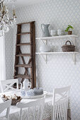 Ladder next to wall-mounted shelves in dining room with diamond-patterned wallpaper