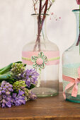Hyacinths next to bottles decorated with fabric trim and fabric flowers