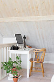 Simple office area under wood-clad sloping ceiling