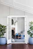 Open double door flanked by house plants, view of the living room with armchair and fireplace