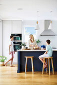 Woman with sons in open kitchen with cows island