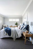 Double bed with pillows and blue bed headboard in the bedroom with light gray walls
