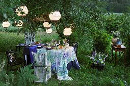 Set table and chair with matching covers below illuminated lanterns in garden
