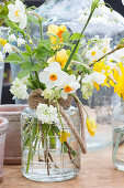 Bouquet of various types of narcissus in glass vase