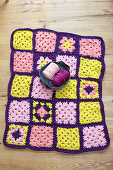 Crocheted blanket in purple, pink and yellow made from jersey yarn