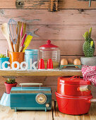 Kitchen utensils, groceries and cacti on wooden shelves