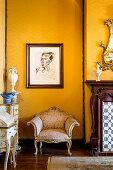 Baroque armchair below portrait on yellow wall