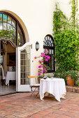 Tisch mit Tischtuch im mediterranen Hof mit Terracottafliesen