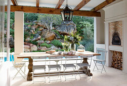Long oak table and folding chairs on roofed terrace with tiled floor and view of planted rock face