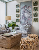 Sisal trunk used as coffee table, wicker stools and decorative tapestry on wall in seating area