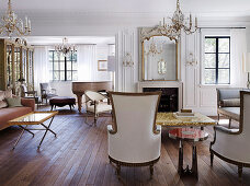 French armchairs in elegant salon with fireplace and chandeliers