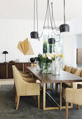 Designer lamp above dining table and elegant leather chairs