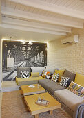 Modern grey and mustard-yellow sofa in front of photo mural and brick wall