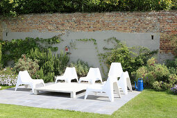 White plastic chairs on terrace in front of garden wall