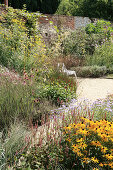 Natural-style herbaceous borders, paths and brick wall in garden late summer