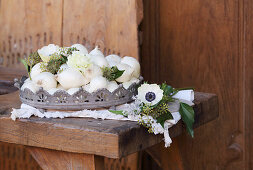 White onions, carnations, anemones and ivy in metal basket