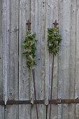 Gesteck aus Efeu auf Metallsteckern vor einer verwitterten Holzwand