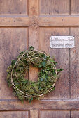 Wreath of ivy leaves and ivy flowers on old wooden door