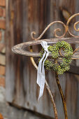 Heart-shaped wreath of ivy berries with ribbon on rusty metal frame