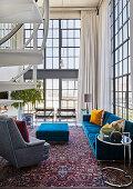 Blaue und graue Polstermöbel in offenem Wohnraum mit Glasfront und doppelter Raumhöhe