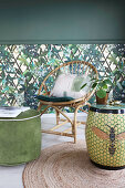 Ceramic stool and wicker chair in front of jungle-patterned wallpaper