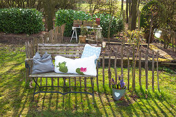 Cushions on garden bench against paling fence
