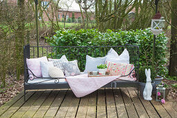 Cushions, blanket and wicker tray on garden bench and rabbit ornament on terrace