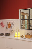 Illuminated bottles in kitchen with red wall and interior window