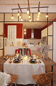 Festively set table in front of open-plan kitchen with red wall