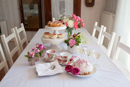 Dome cake, sparkling wine and roses on table set for afternoon coffee