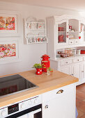 Island counter with wooden worksurface in front of plate rack on wall and white dresser